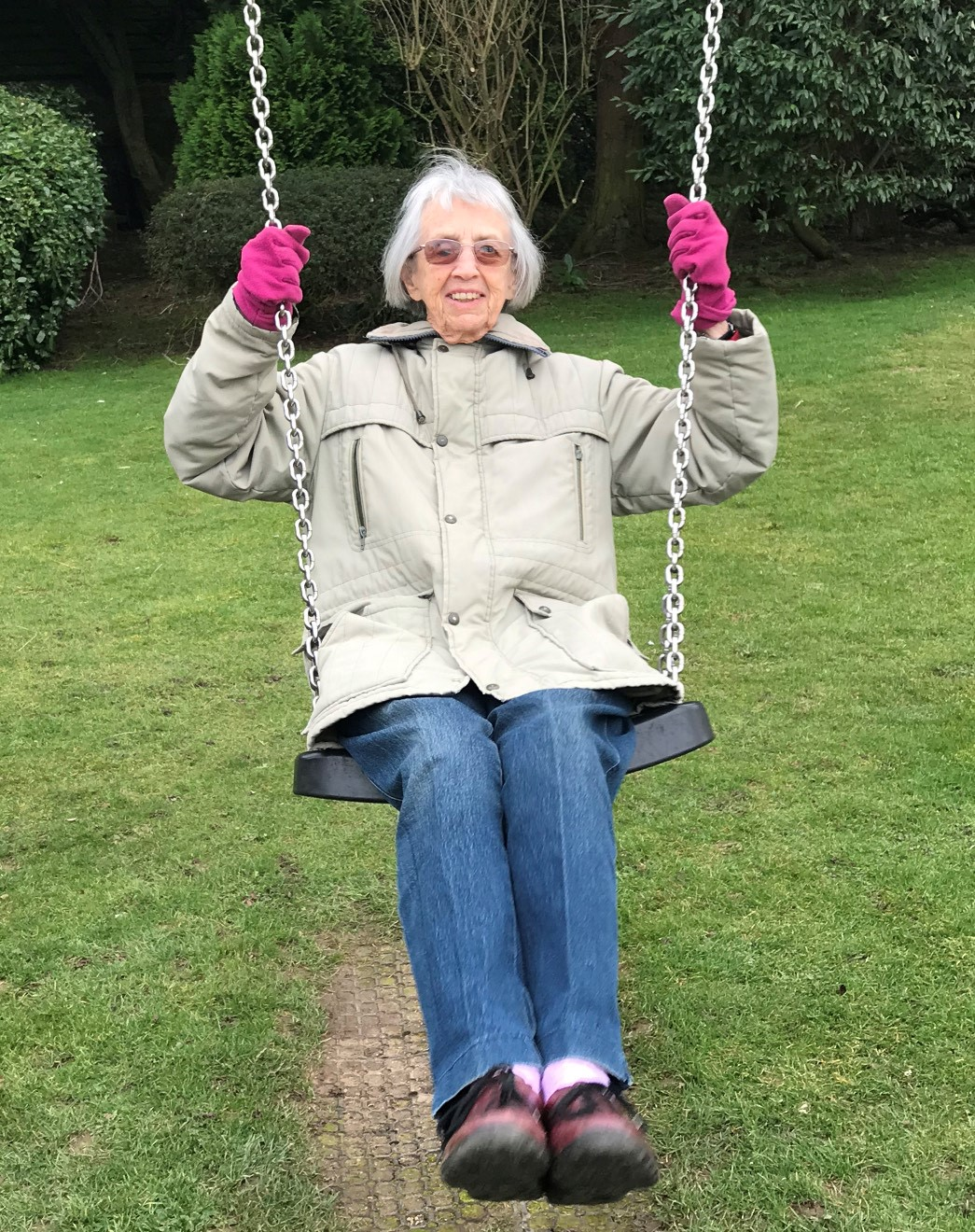 Alison's mum Janet on a swing on holiday