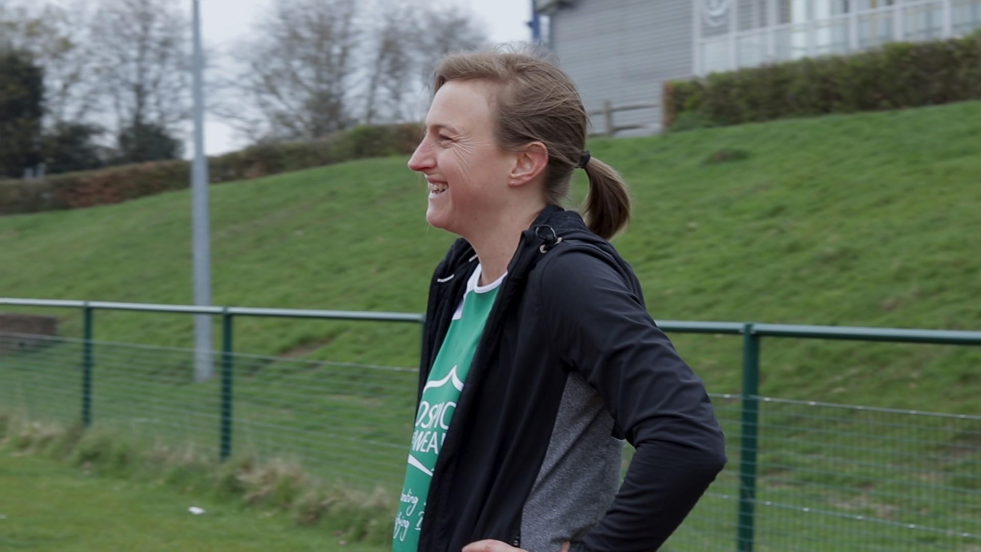 Carla smiling at running track