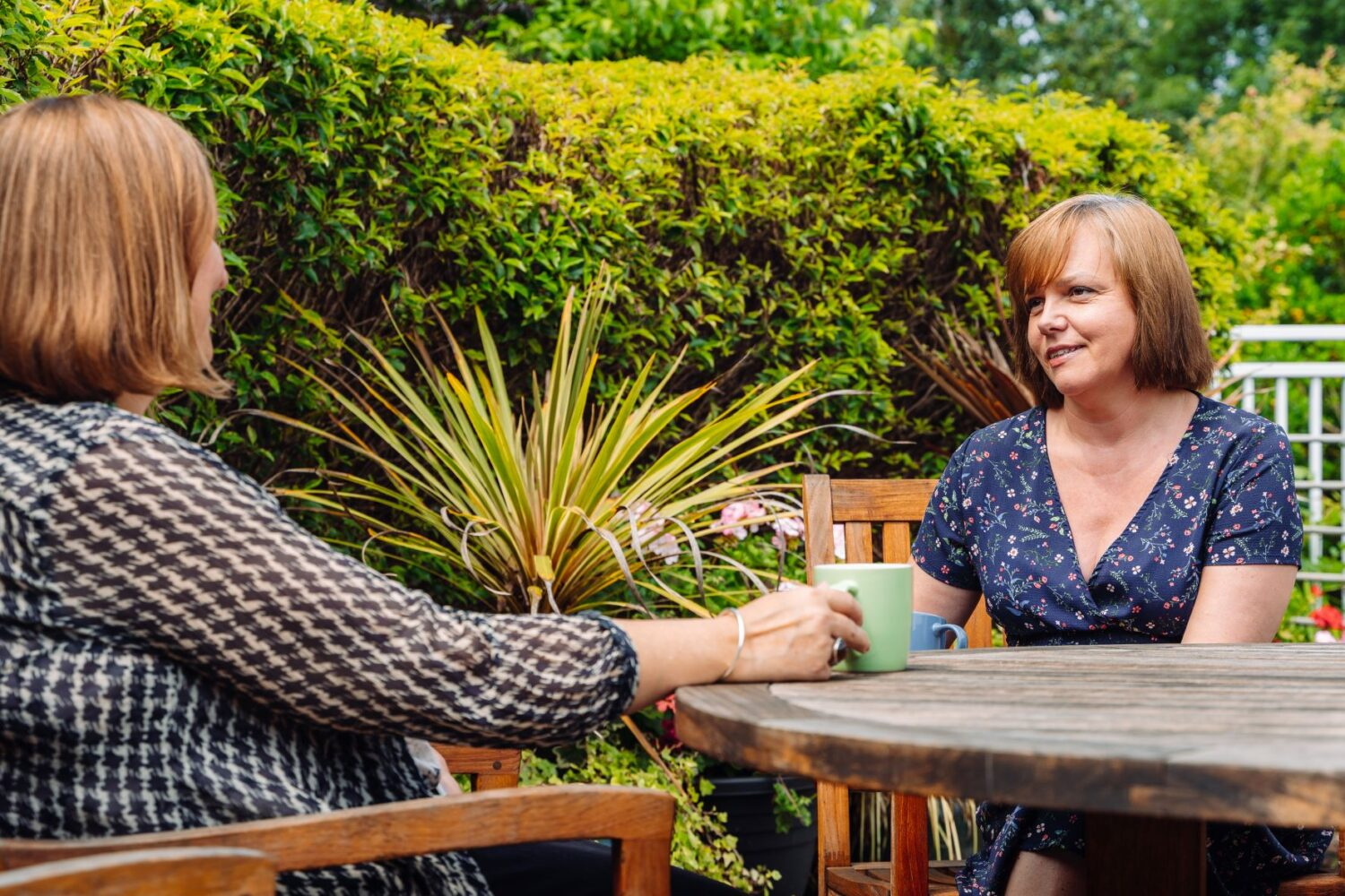 Counsellor and client outside with cup of tea
