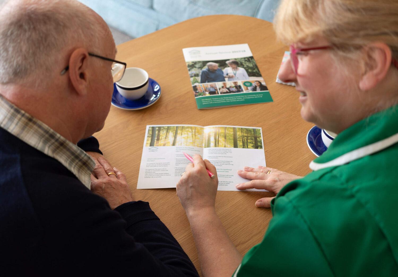 Hospice staff explaining leaflet