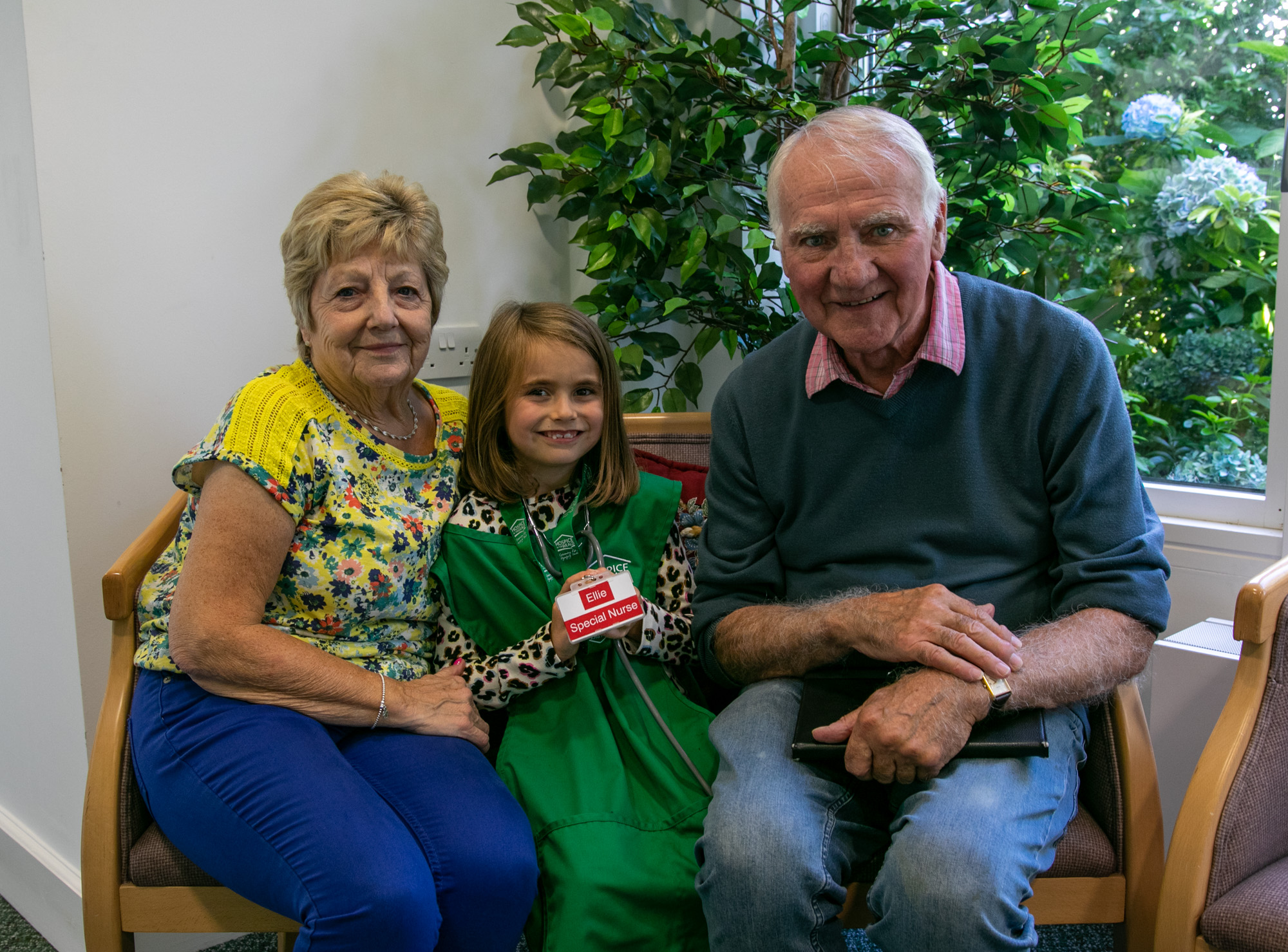 Tim and Gill sitting with their grandaughter Ellie in the cafe