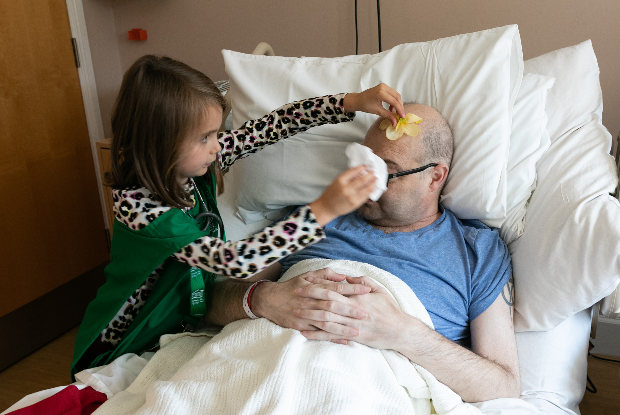 Ellie rubbing a cold flower on her Dad's head to help ease his symptoms