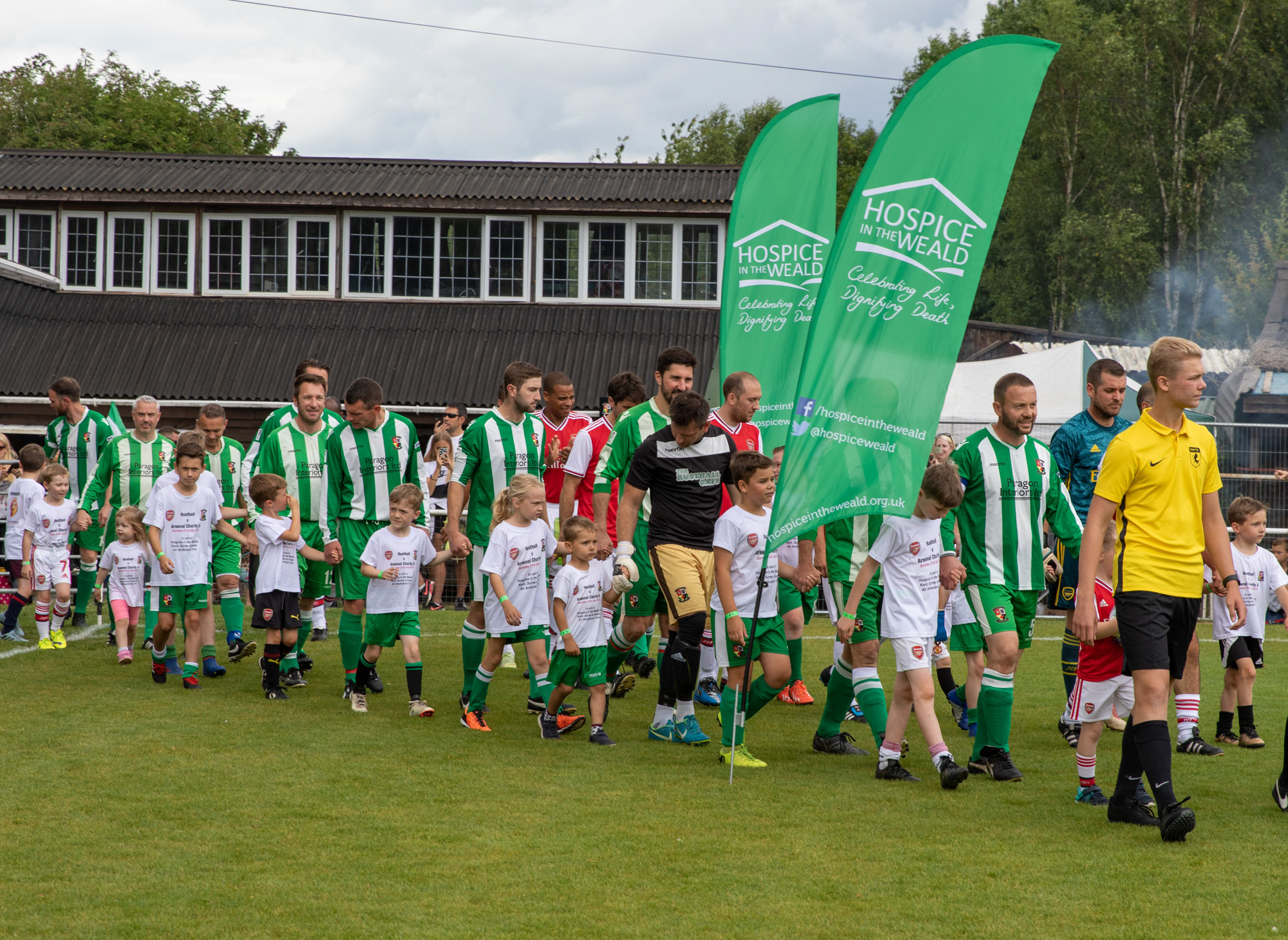Rusthall FC walking on pitch with our flags in hand