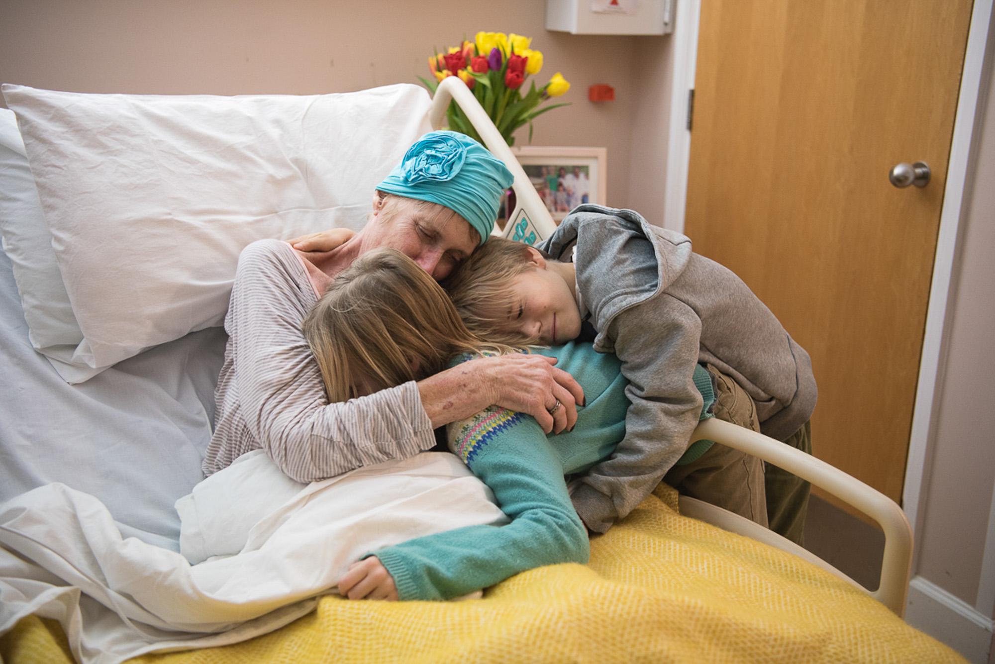 patient on ward hugging her grandchildren