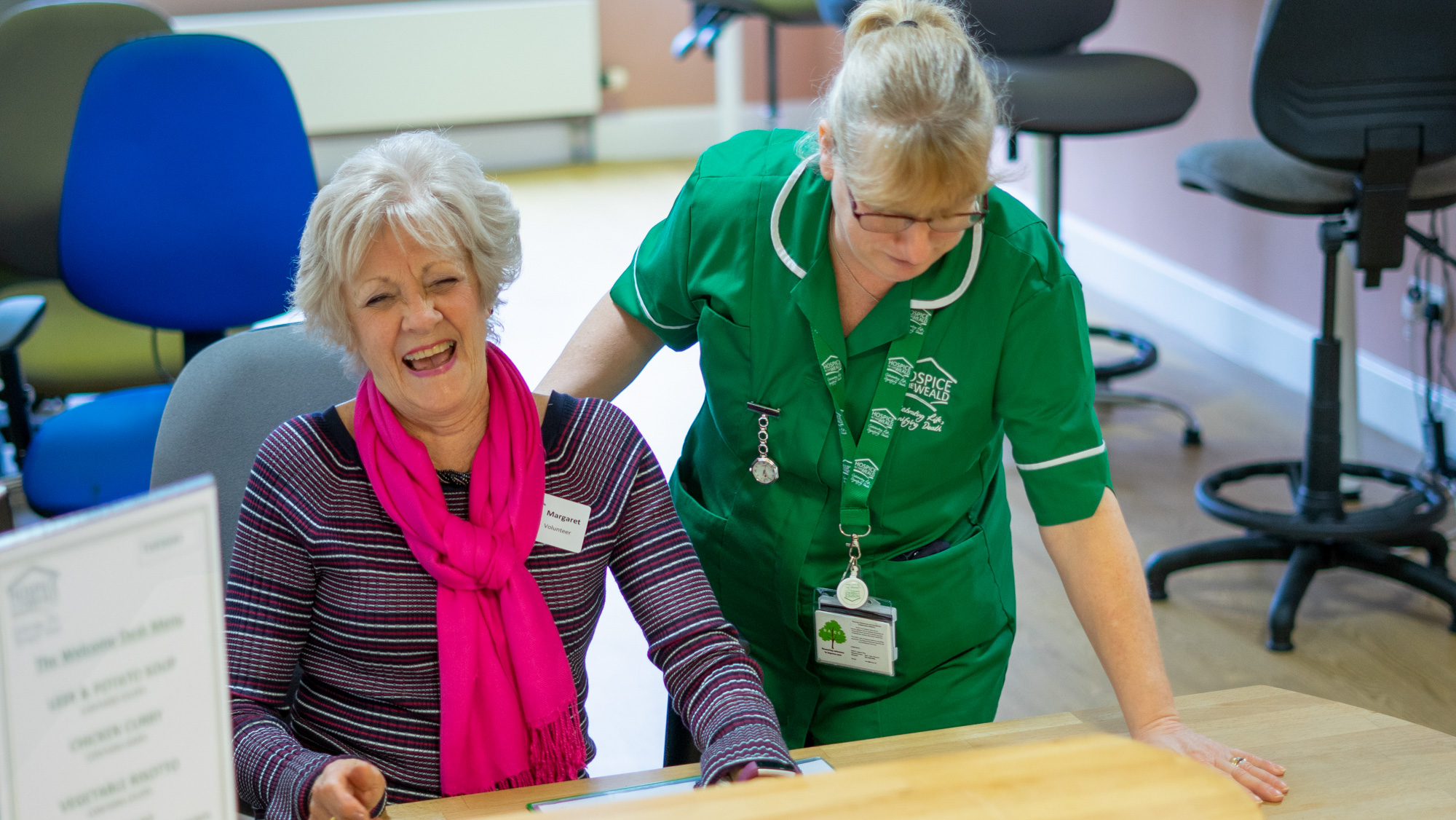Margaret volunteer on the ward laughing with nurse
