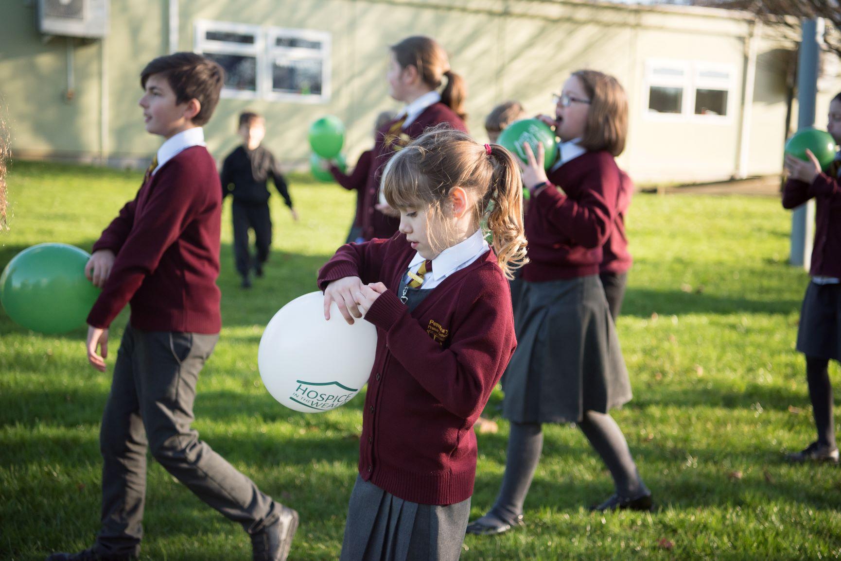 School Children Blowing up Balloons