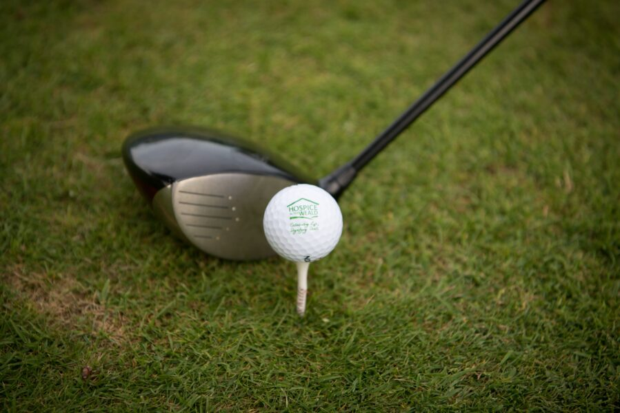 Golf Ball with Hospice in the Weald Logo on next to club