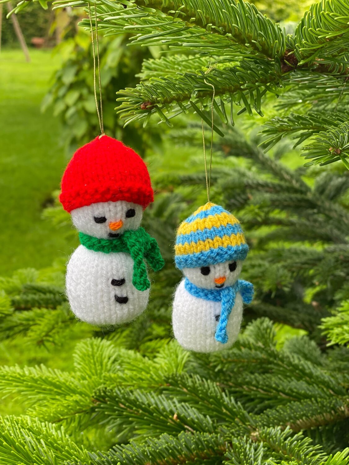 Stitched Snowmen hanging from a fir tree